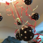Simple polka dotted bulbs are hung from the chandelier at different heights with curling ribbon.