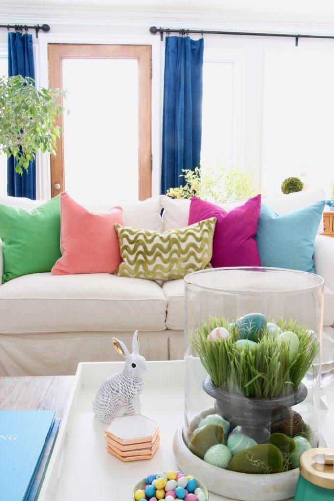 Meme_HIll_Studio_Amie_freling_easter_decorating_livingroom_colorful_ideas_pillows_homeGoods_art_flowers_sofa_white_slipcoveredDecor_rabbit_eggs_velvet_pillows