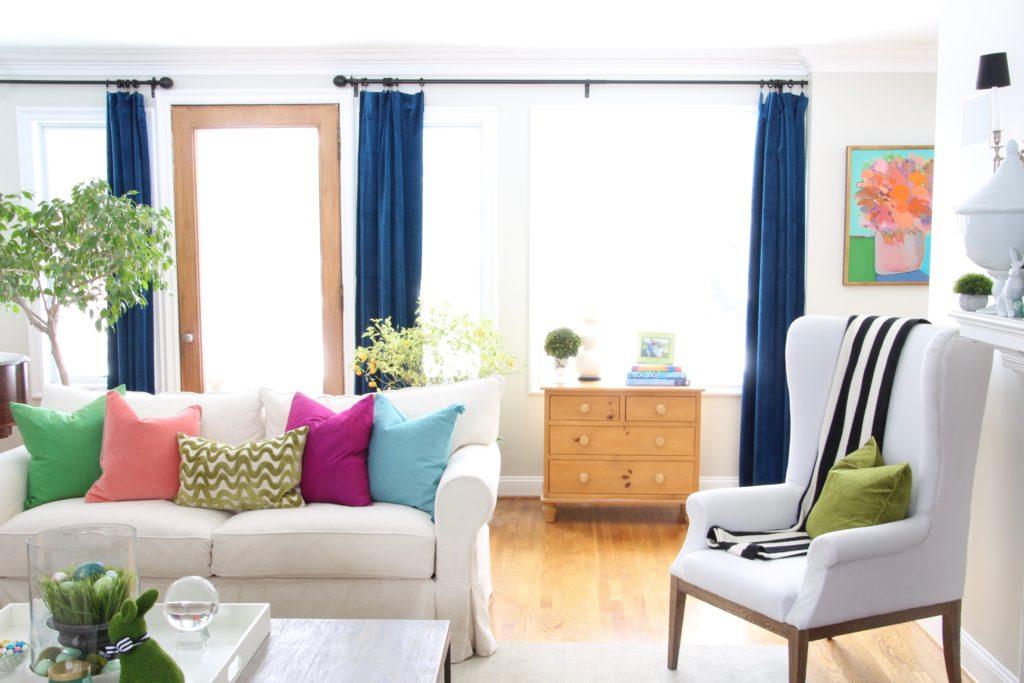 Meme_HIll_Studio_Amie_freling_easter_decorating_livingroom_colorful_ideas_pillows_homeGoods_art_flowers_sofa_white_slipcovered_velvet_curtains